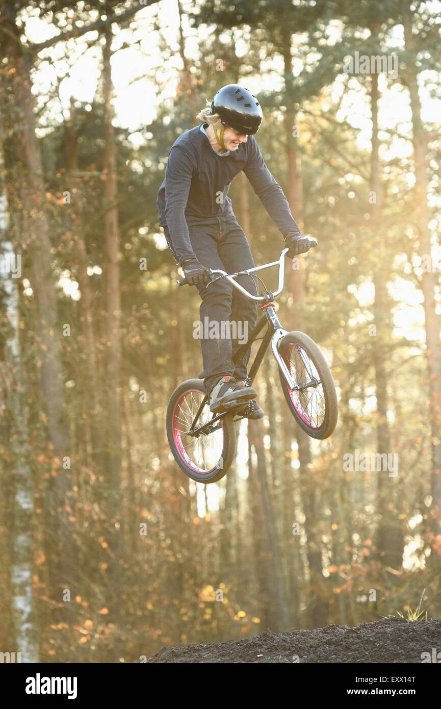 Teenager jumping in the air with his bmx bike - Stock Image