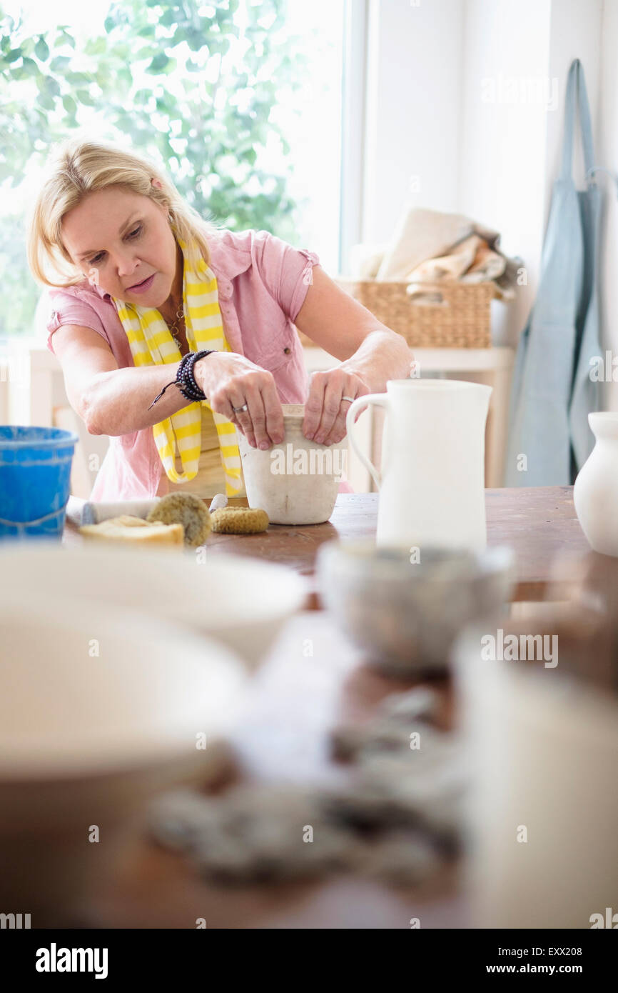 Mature woman making pottery in studio - Stock Image