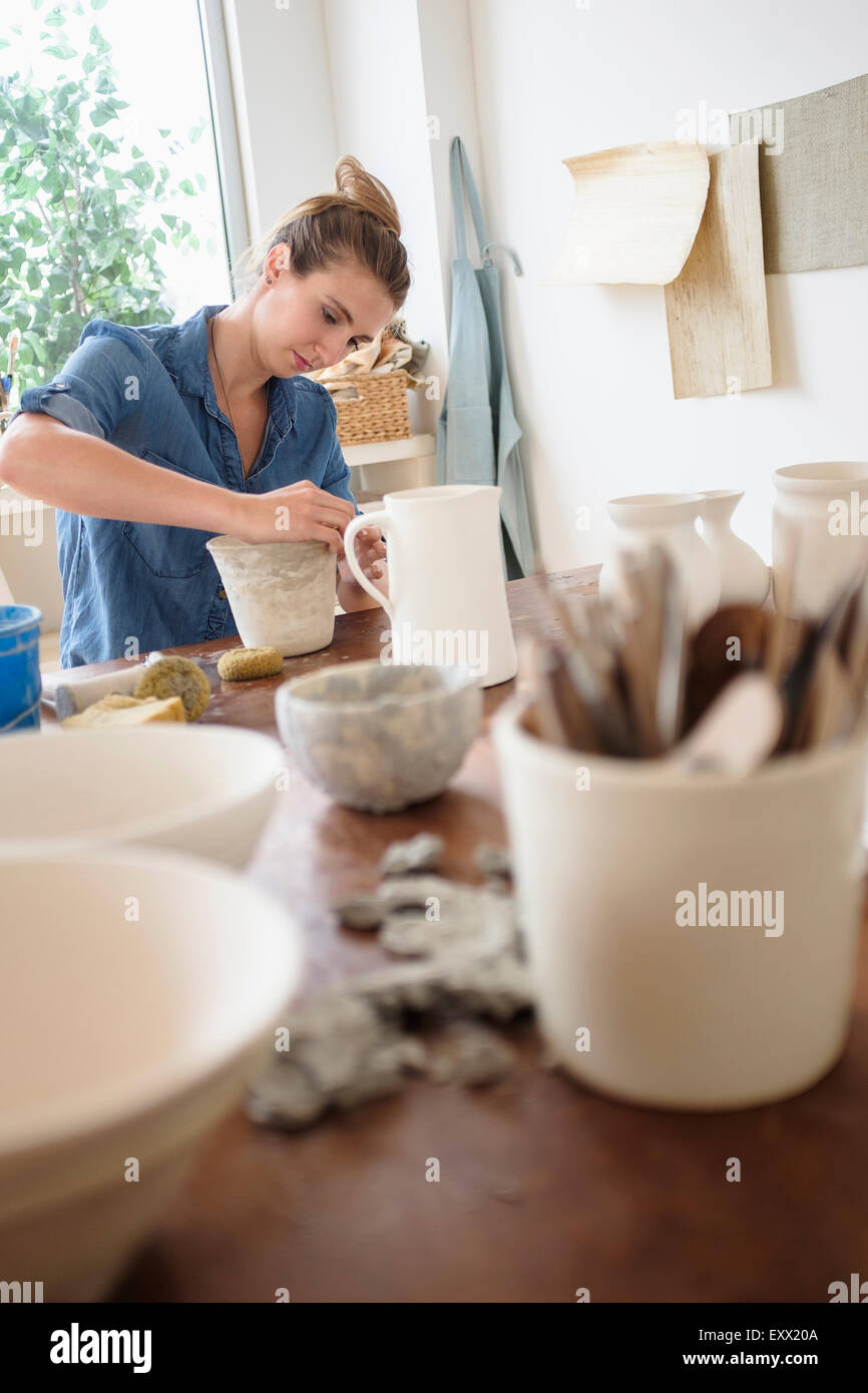 Young woman making pottery in studio - Stock Image