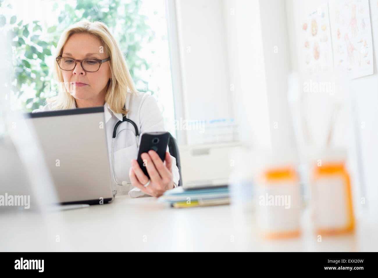 Doctor working with laptop in her office - Stock Image