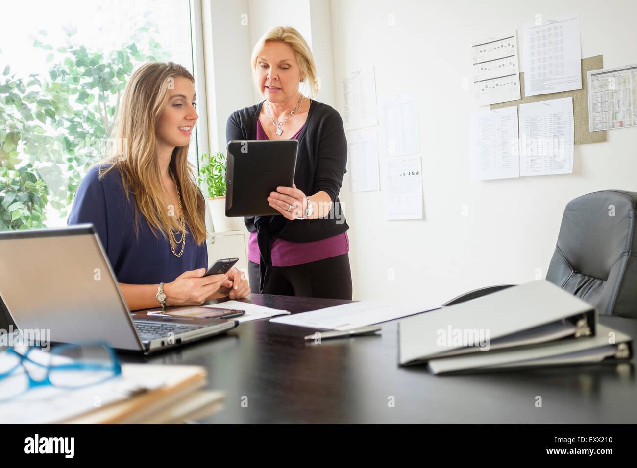 Two business women talking in office - Stock Image