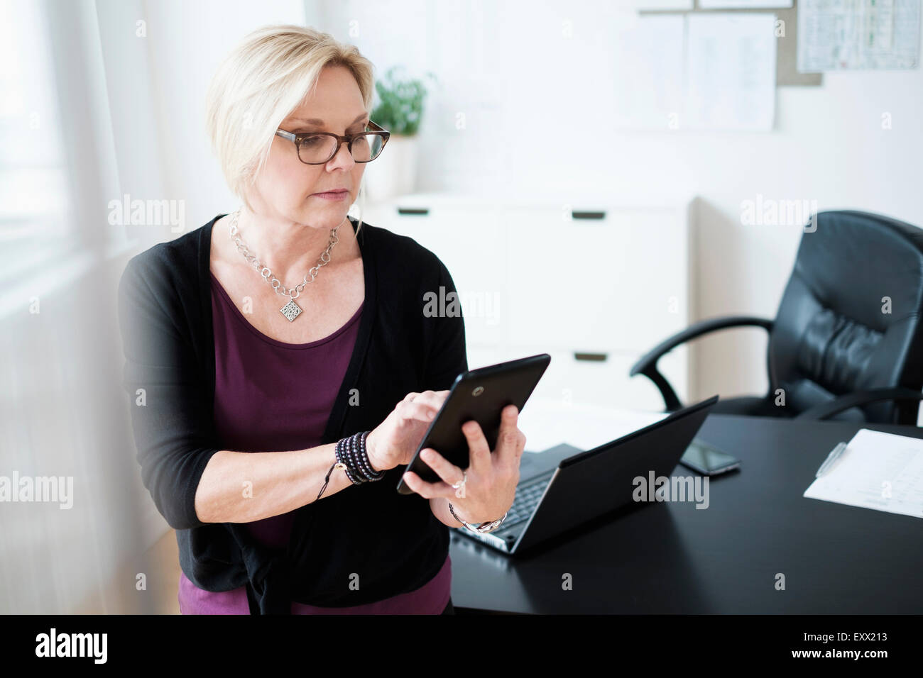 Businesswoman using tablet in office - Stock Image