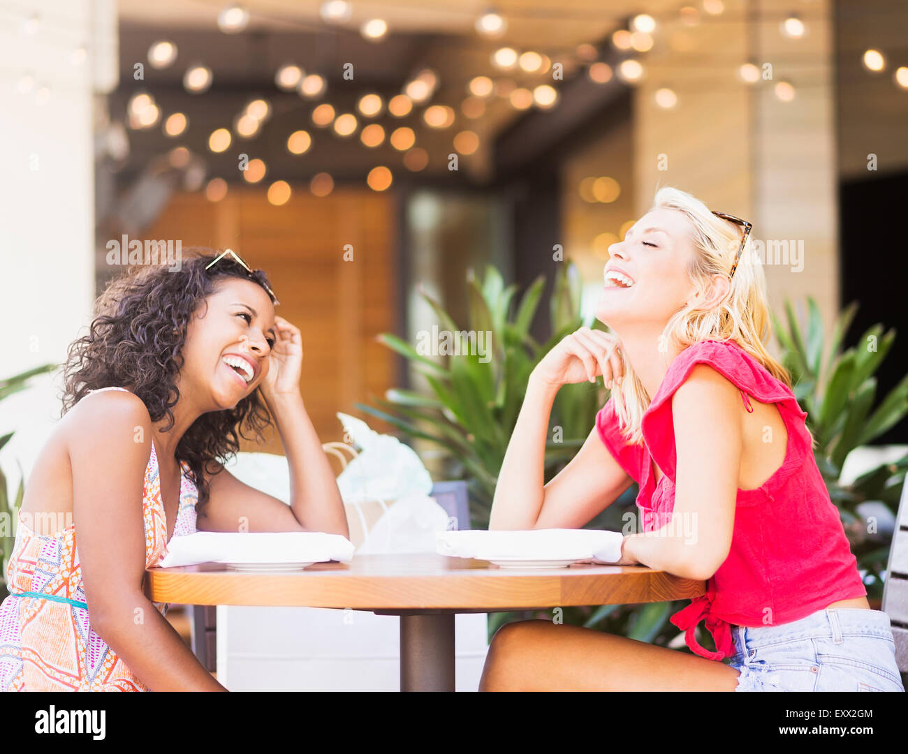 Female friends laughing in street cafe - Stock Image