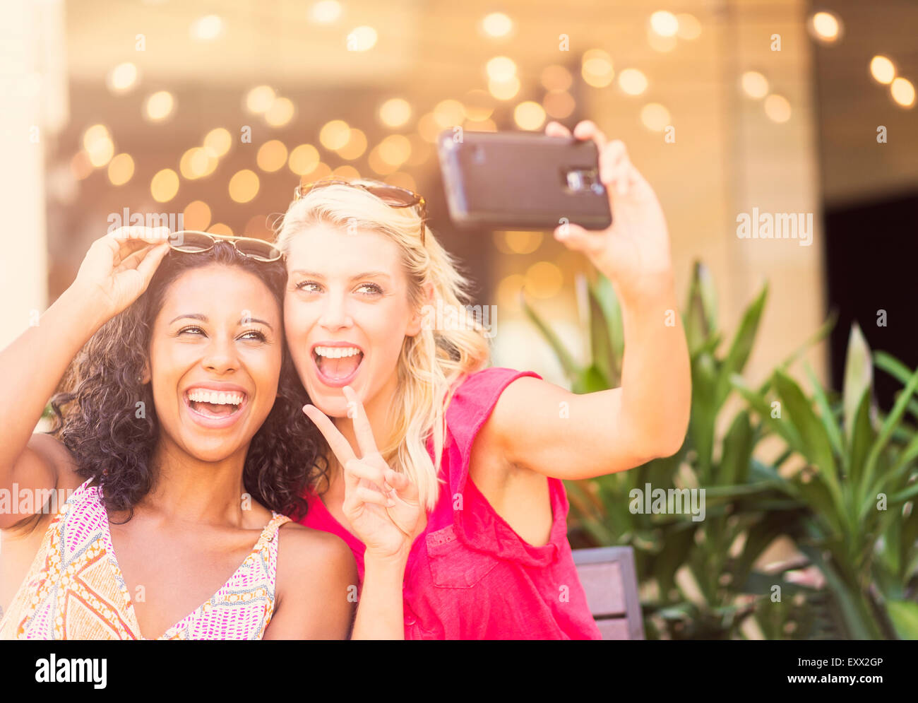 Female friends taking selfie with smart phone in cafe - Stock Image