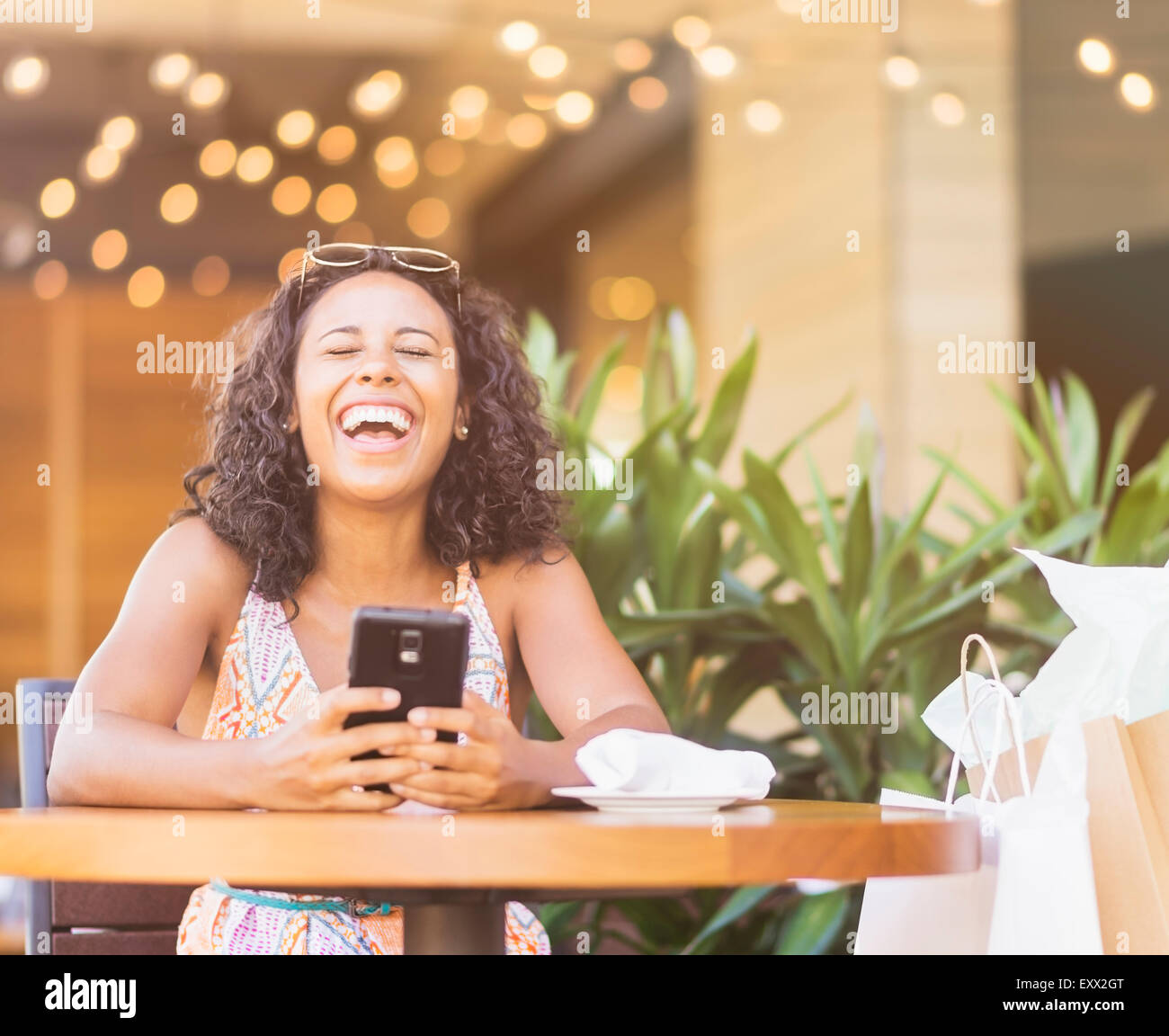 Woman using phone in cafe - Stock Image