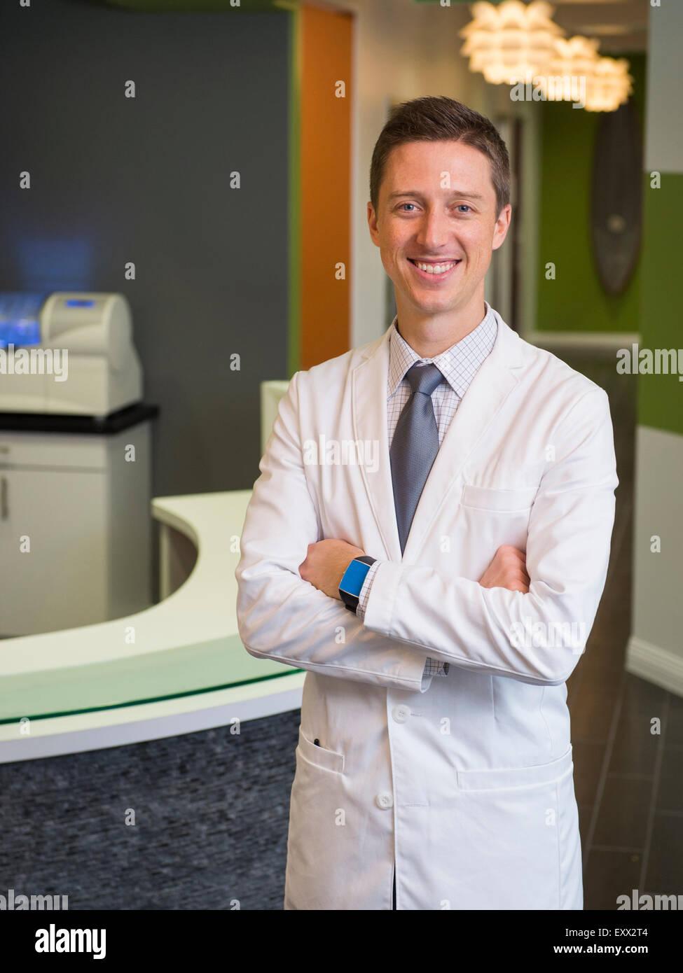 Portrait of smiling dentist - Stock Image