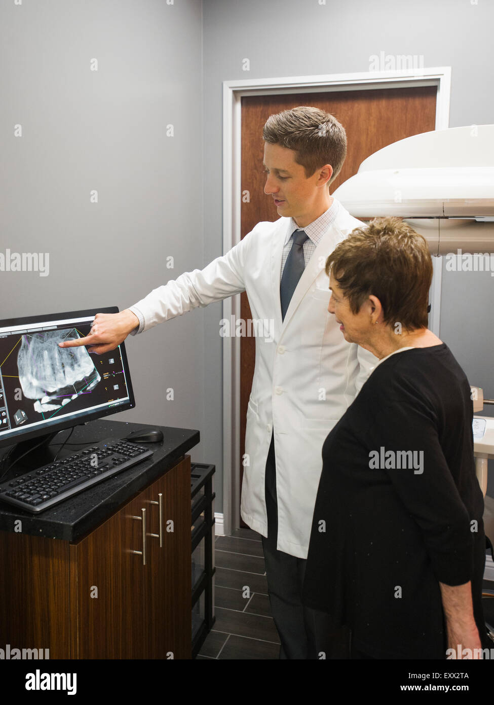 Dentist showing patient x-ray on computer screen - Stock Image