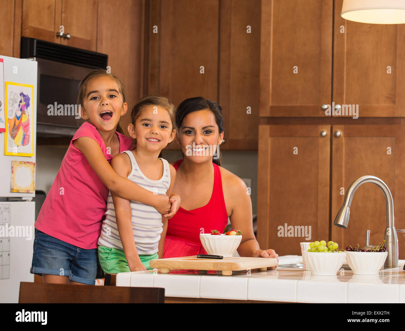 Mother and children (6-7, 8-9) preparing food in kitchen - Stock Image