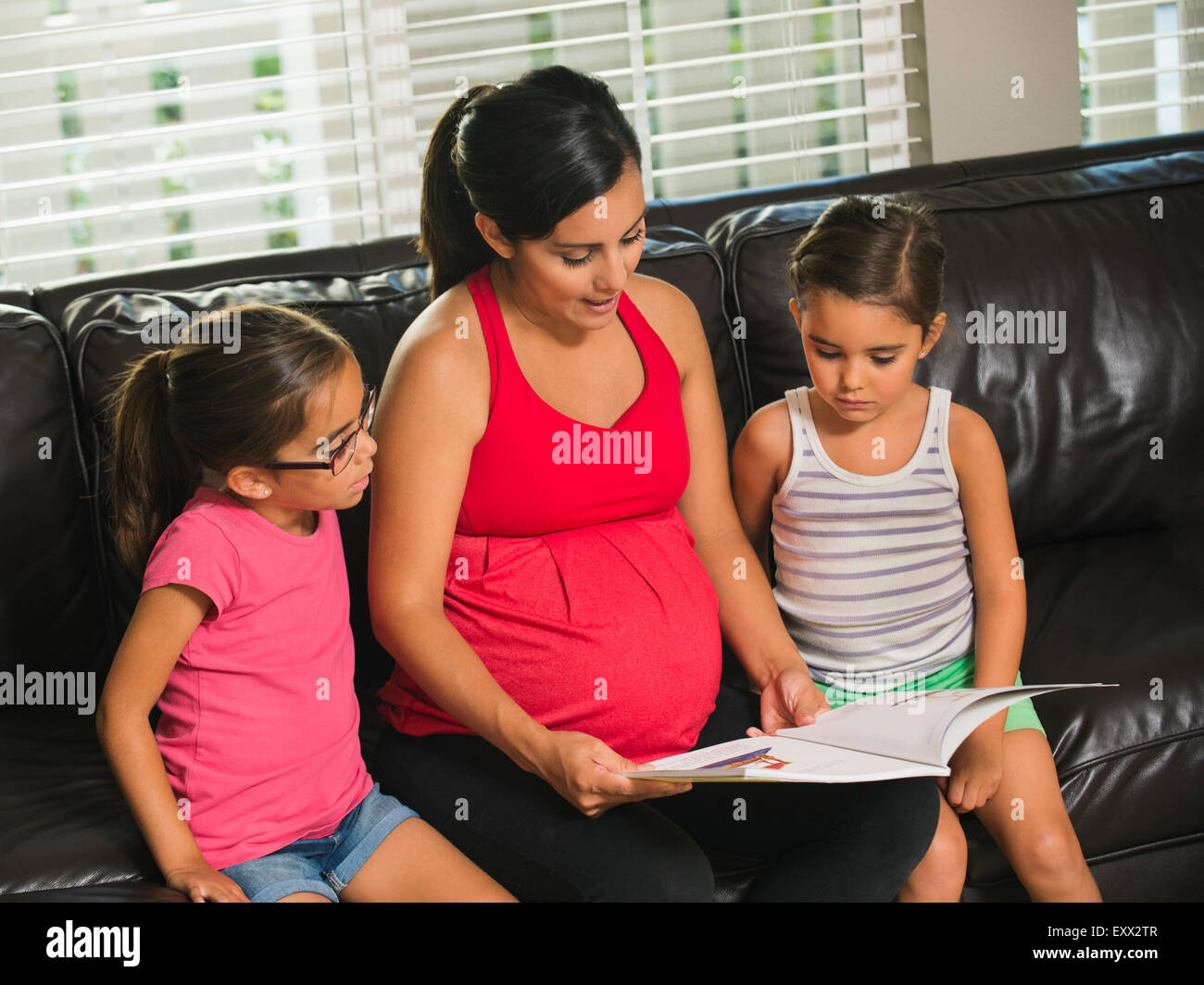 Mother reading to children (6-7, 8-9) - Stock Image