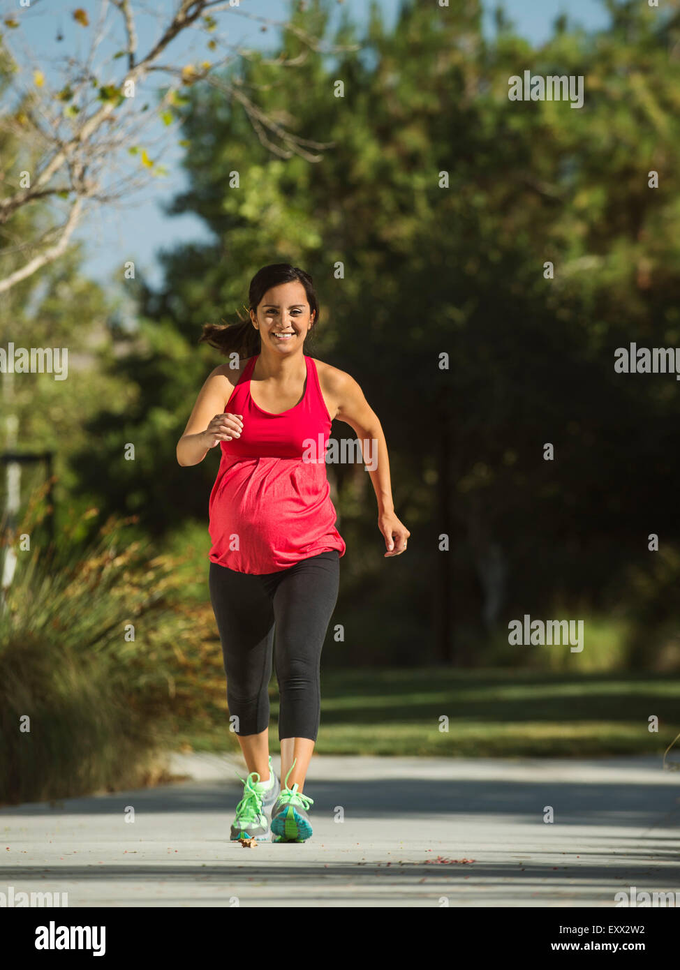 Pregnant woman running outdoors - Stock Image