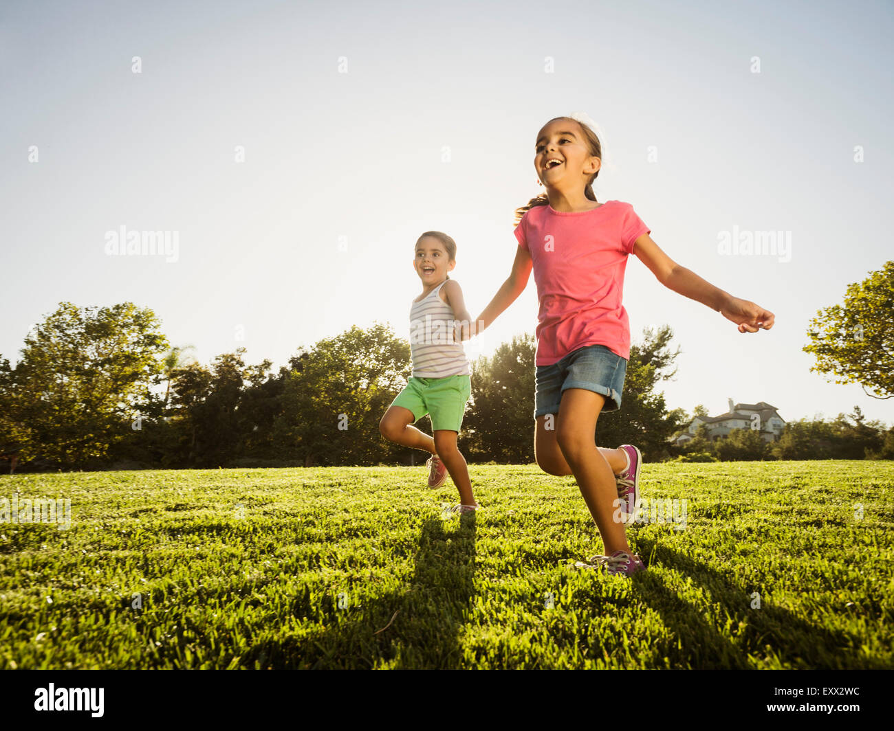 Sisters (6-7, 8-9) playing in park - Stock Image