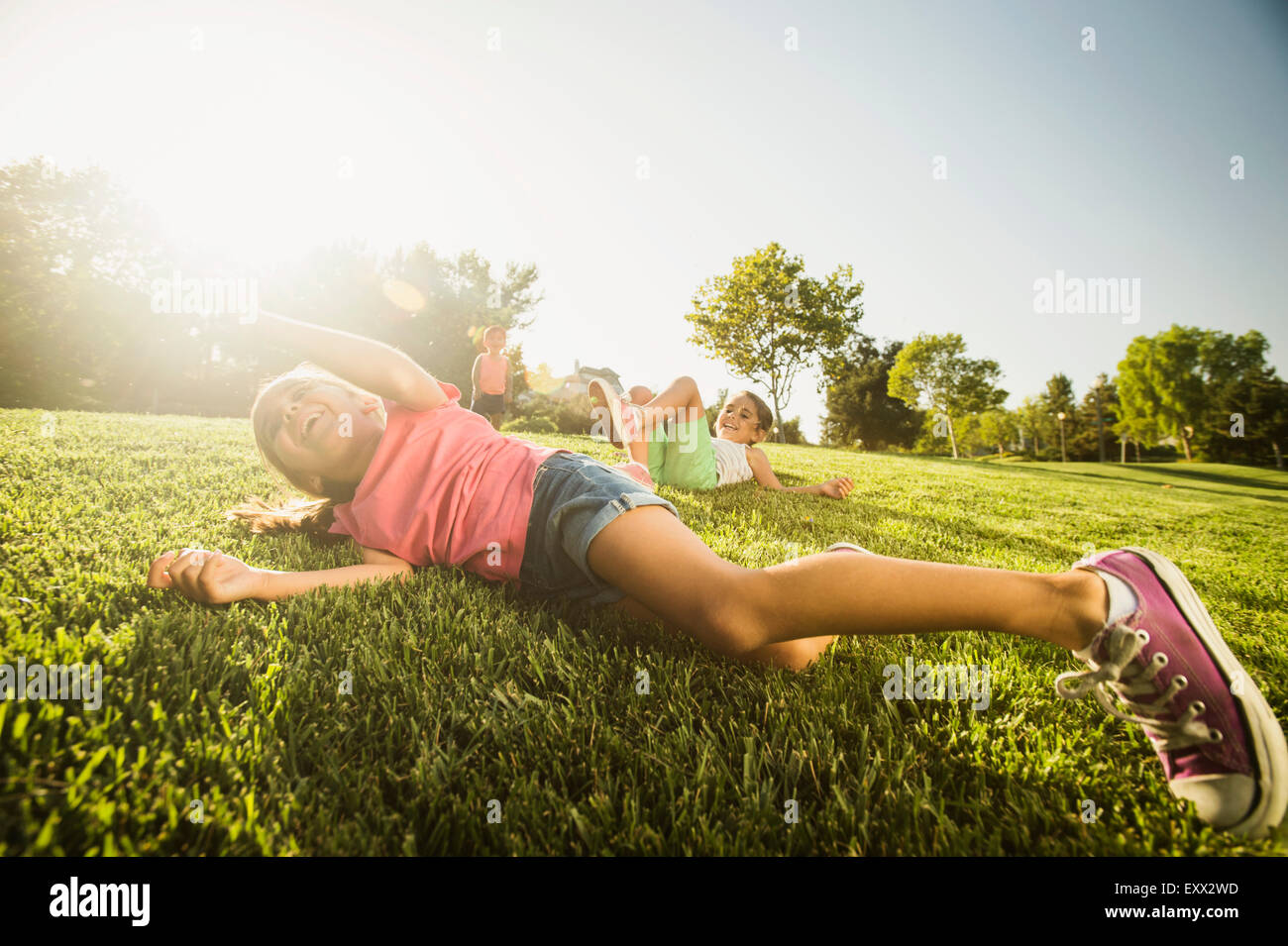 Siblings (2-3, 6-7, 8-9) playing in park - Stock Image