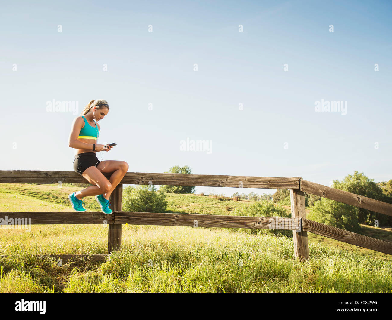 Woman sitting on fence, using smart phone - Stock Image