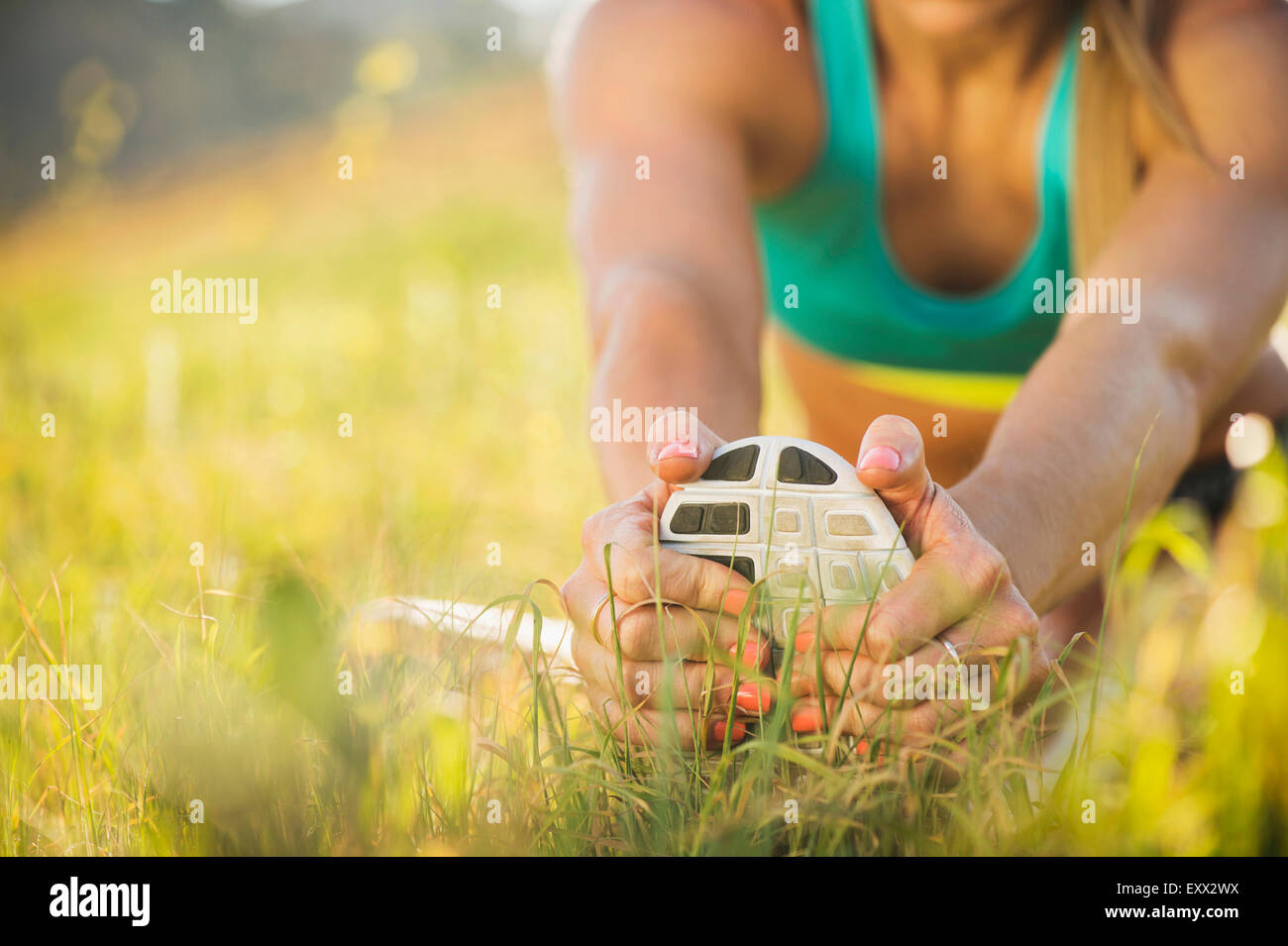 Woman exercising in field - Stock Image