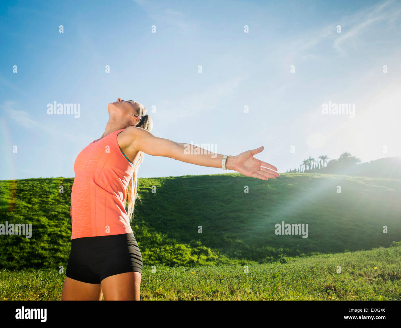 Woman with outstretched arms in field - Stock Image