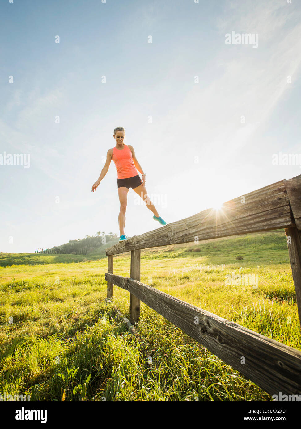 Woman balancing on wooden fence - Stock Image