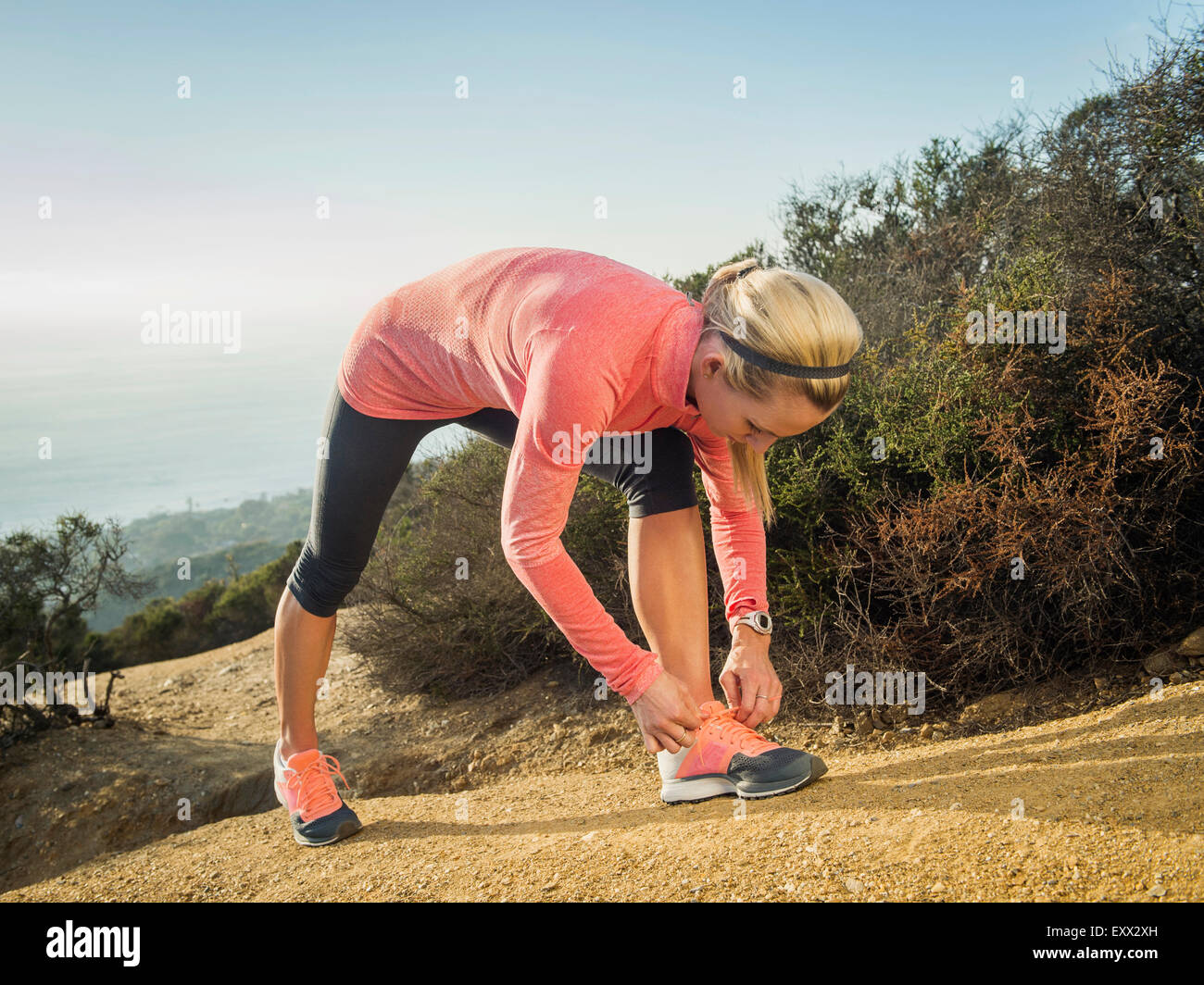 Woman tying shoe - Stock Image