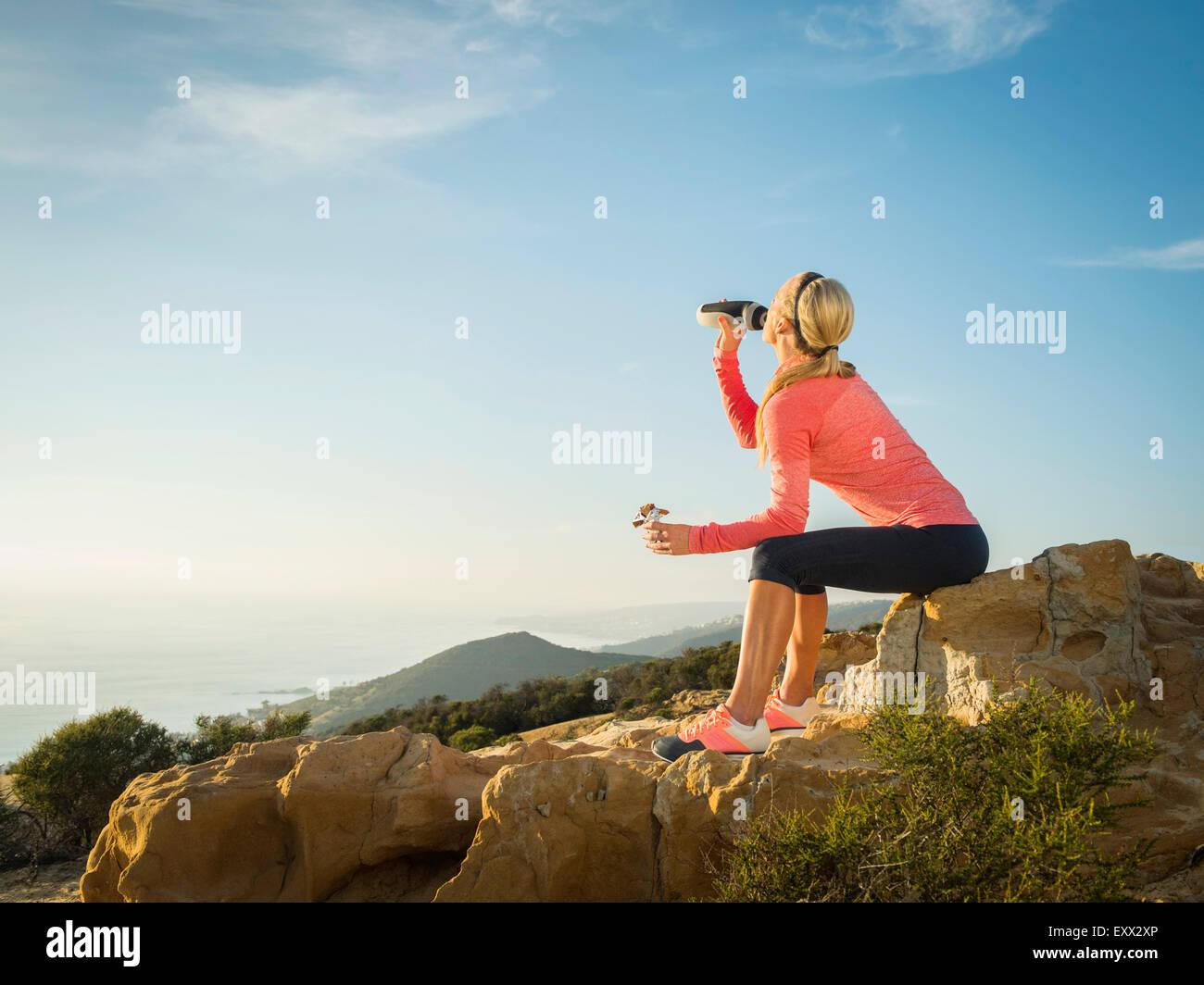 Woman in sportswear drinking water - Stock Image
