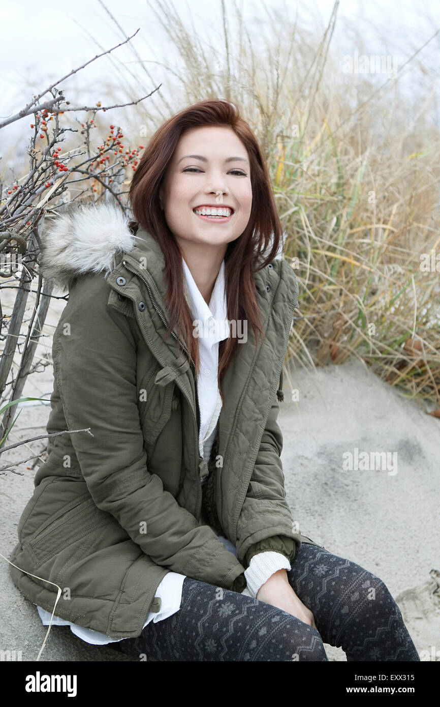 Portrait of woman in parka on winter beach - Stock Image