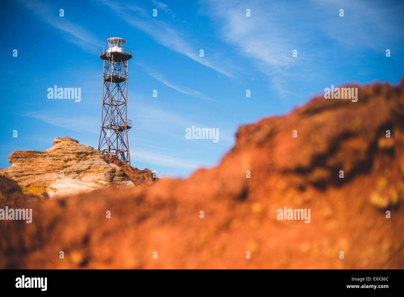 Lighthouse behind red rock at Gantheaume Point, Broome Stock Photo