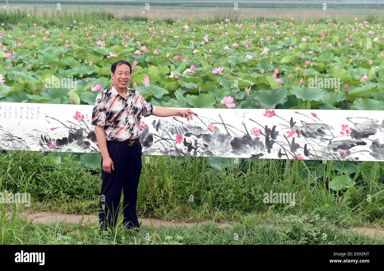(150717) -- LANGFANG, July 17, 2015 (Xinhua) -- Wang Yongquan interprets his lotus painting to spectators before - Stock Image