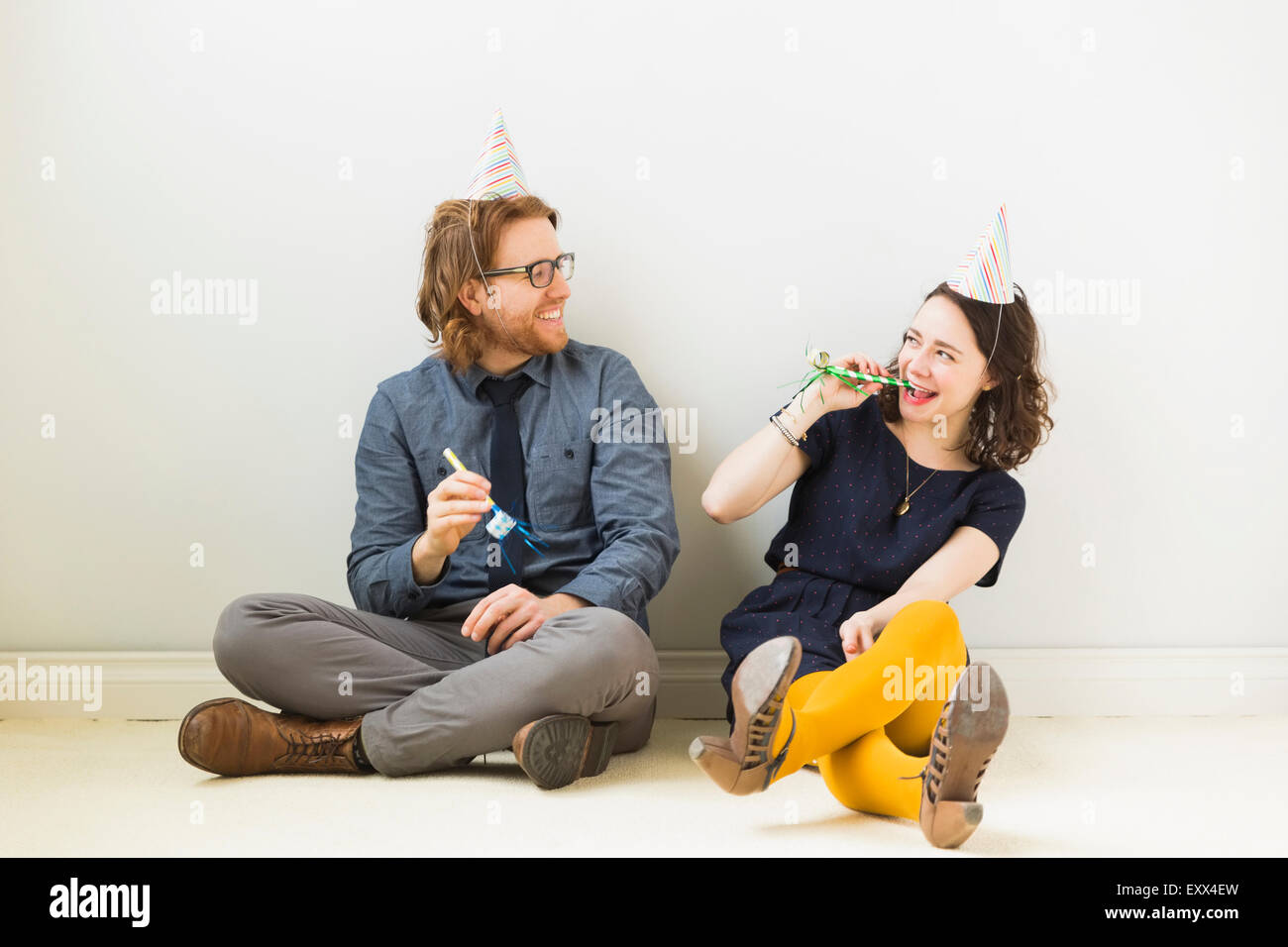 Couple with party horn blowers and party hats sitting on floor - Stock Image
