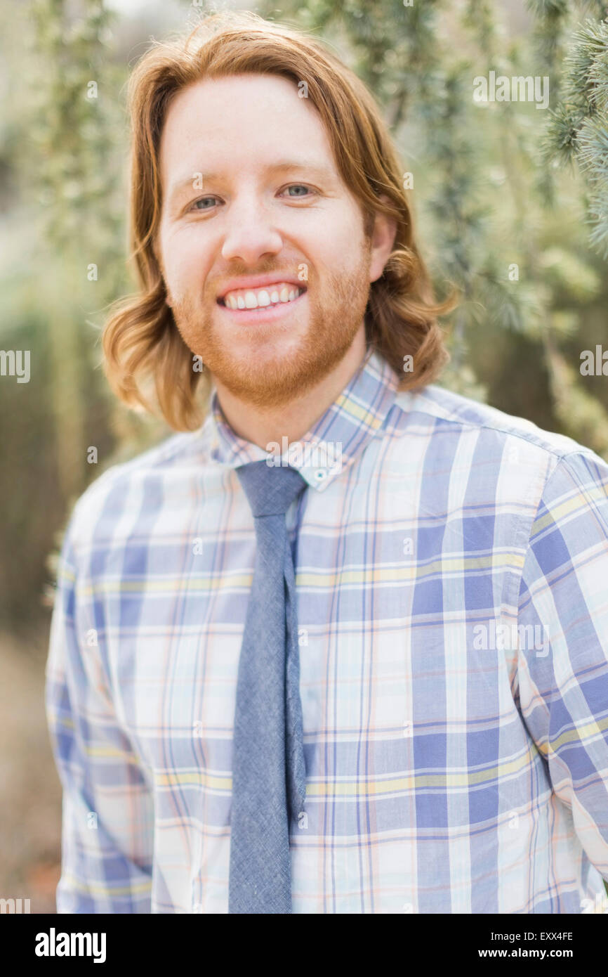 Portrait of smiling man wearing plaid shirt - Stock Image