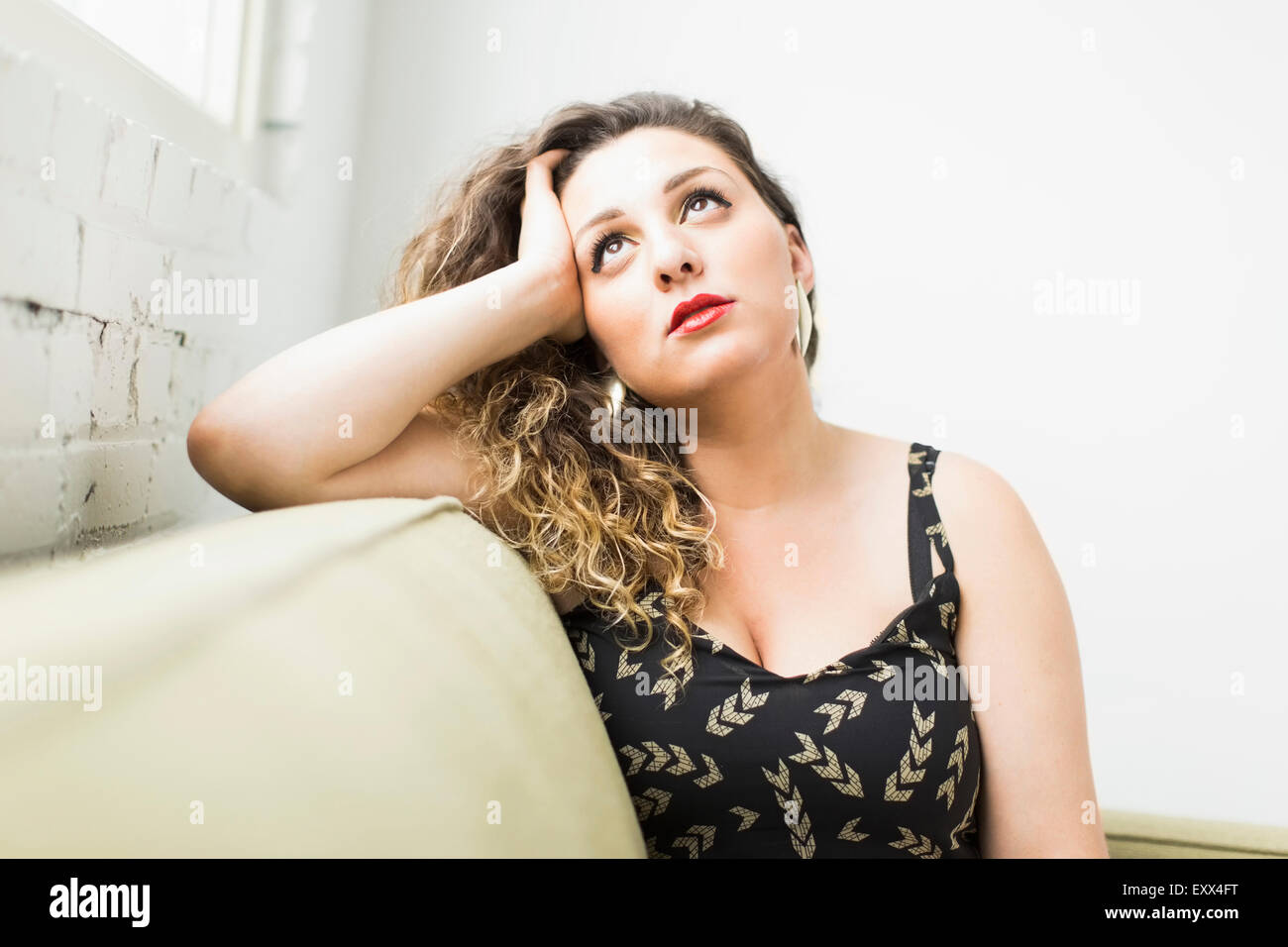 Woman looking up and daydreaming - Stock Image