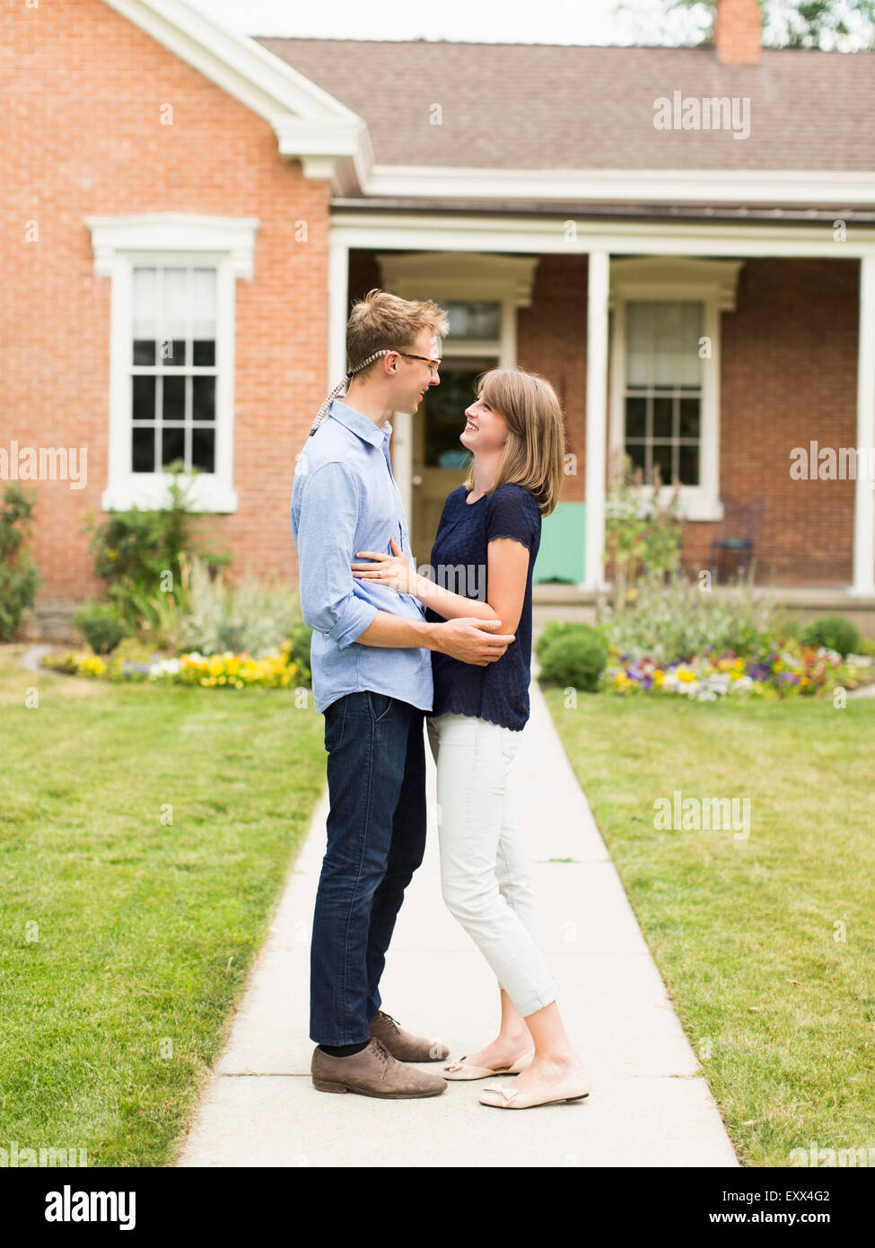 Young couple standing on footpath in front of house - Stock Image