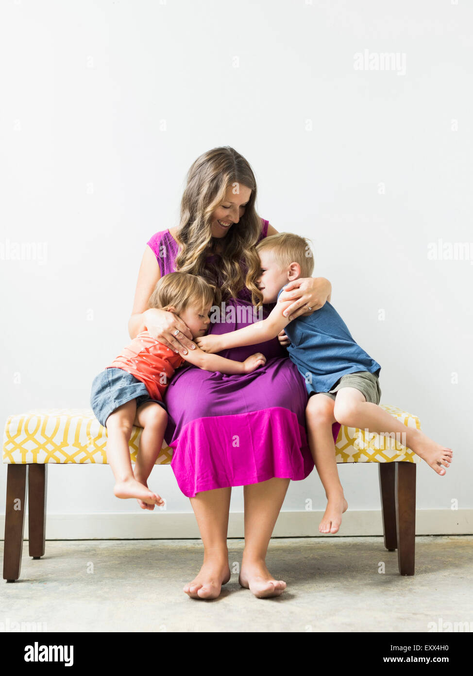 Children (2-3) hugging pregnant mother on bench - Stock Image