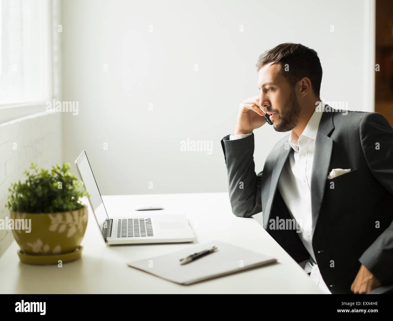 Young man sitting at desk and looking at laptop - Stock Image