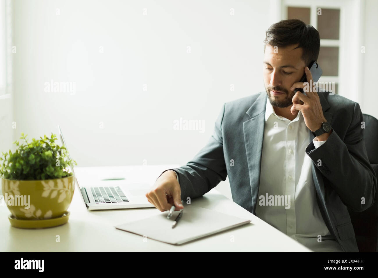 Young man sitting at desk and looking at laptop Stock Photo