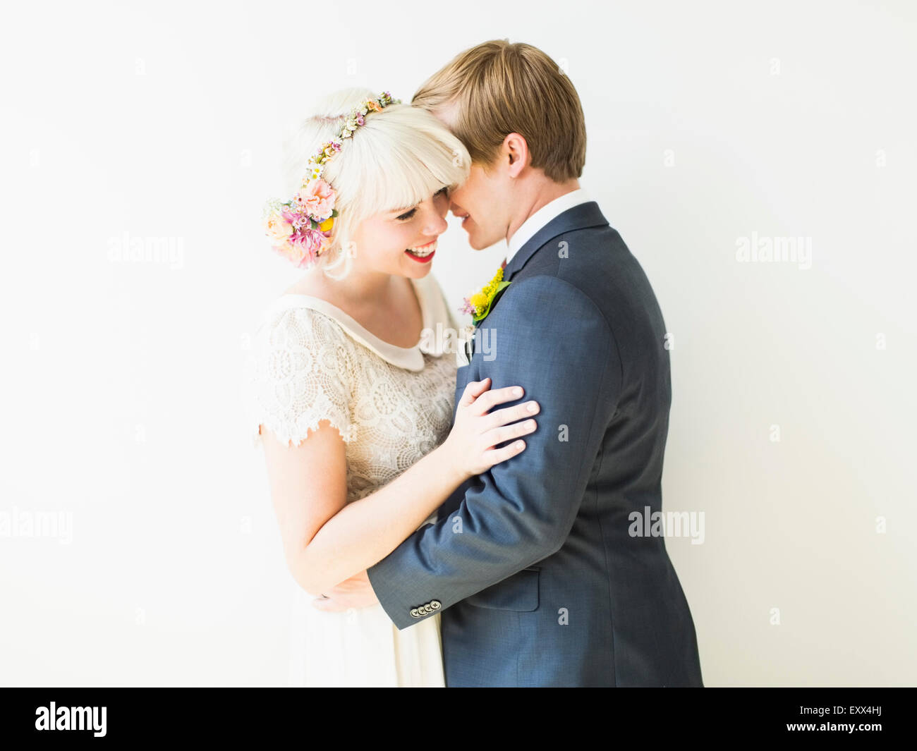 Smiling newlywed couple embracing - Stock Image