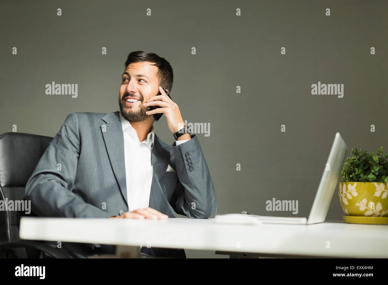 Young man sitting at desk and talking on phone Stock Photo
