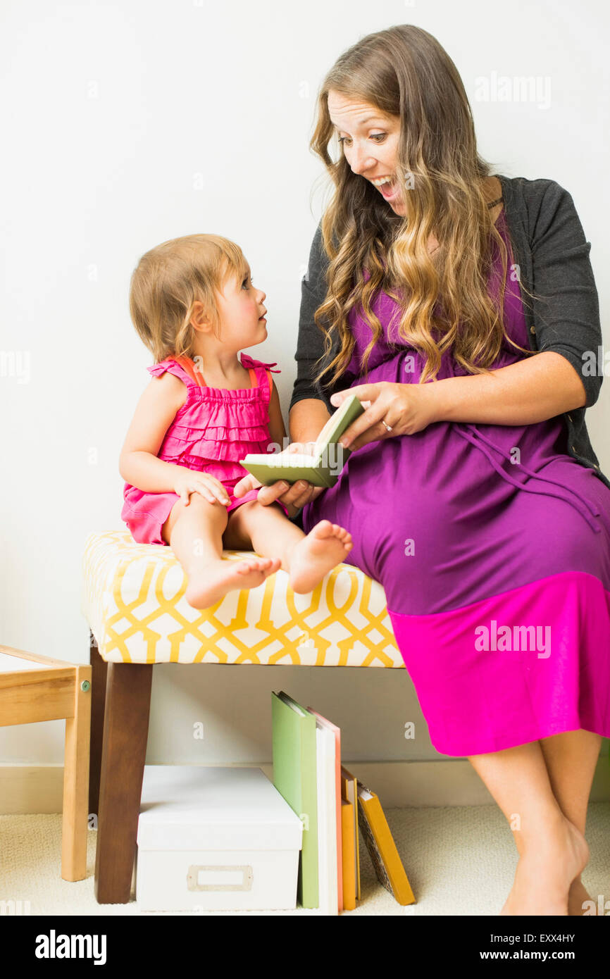 Mother reading to little daughter (2-3) - Stock Image
