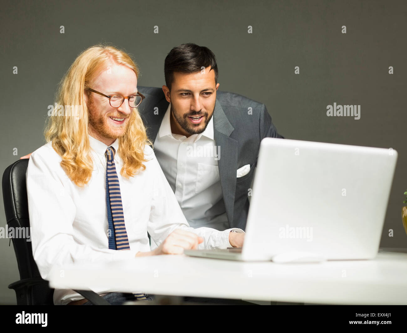Businessmen looking at laptop in office - Stock Image