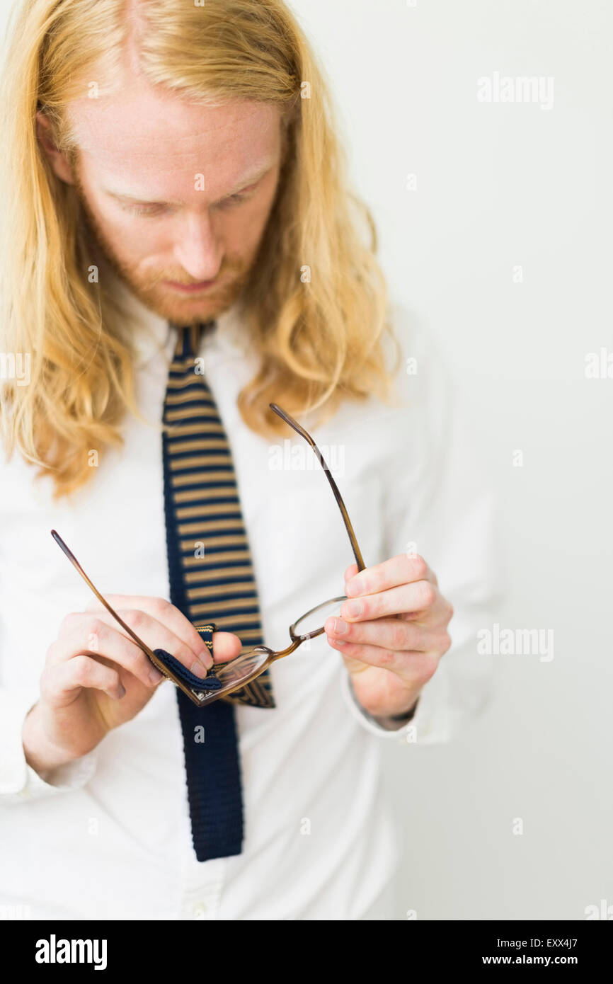 Blond man wiping glasses - Stock Image
