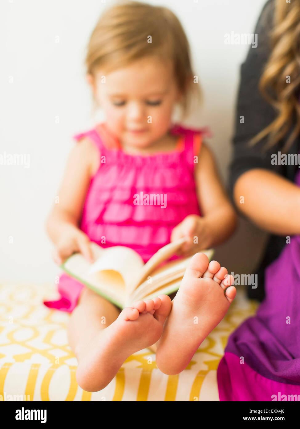 Little girl (2-3) holding book - Stock Image