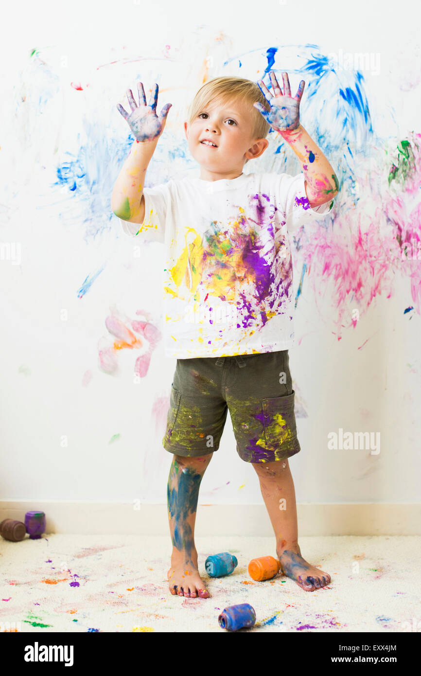 Boy (2-3) showing hands after painting on wall - Stock Image