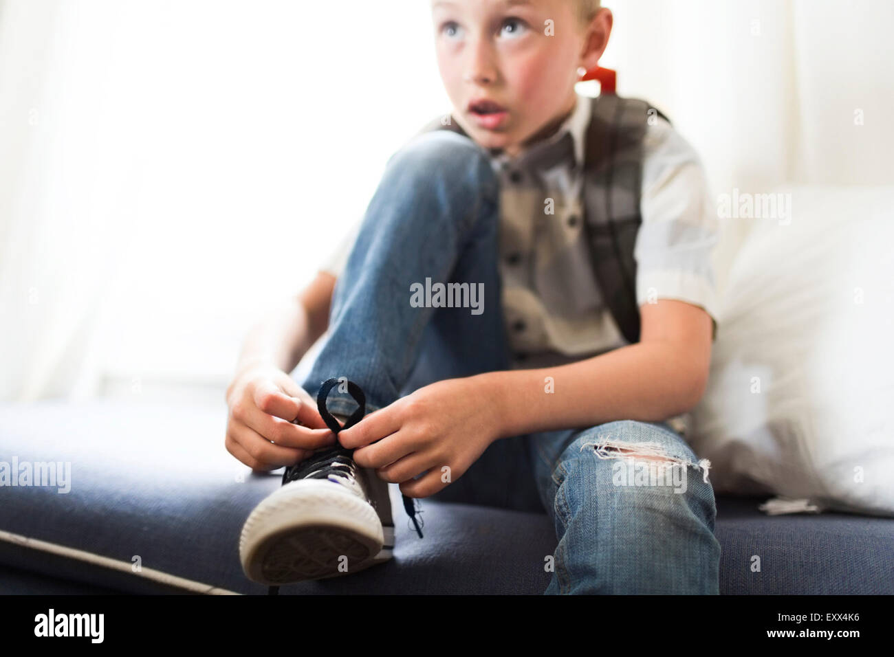 Boy (6-7) tying shoes - Stock Image