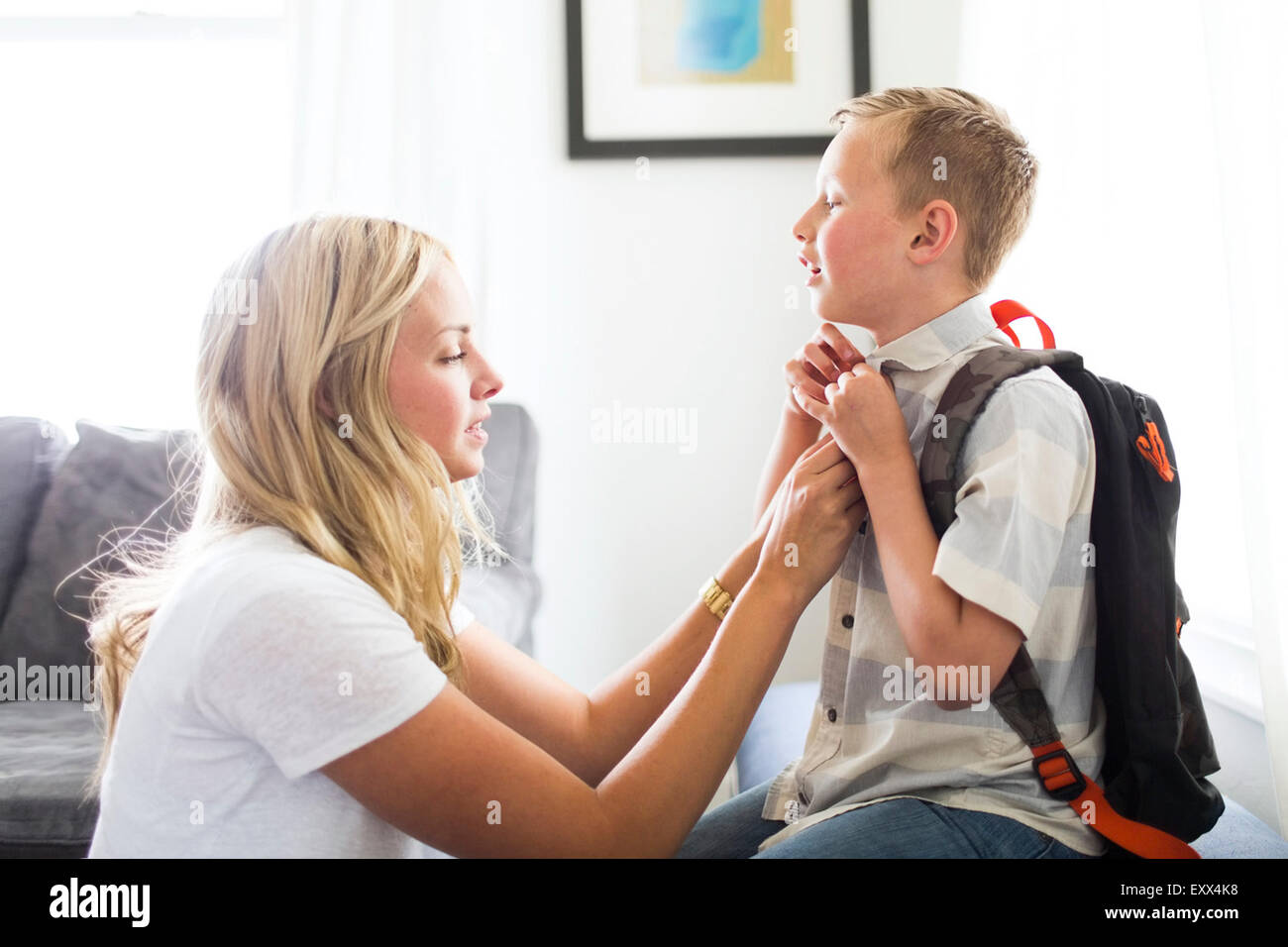Mother helping son (6-7) buttoning shirt - Stock Image