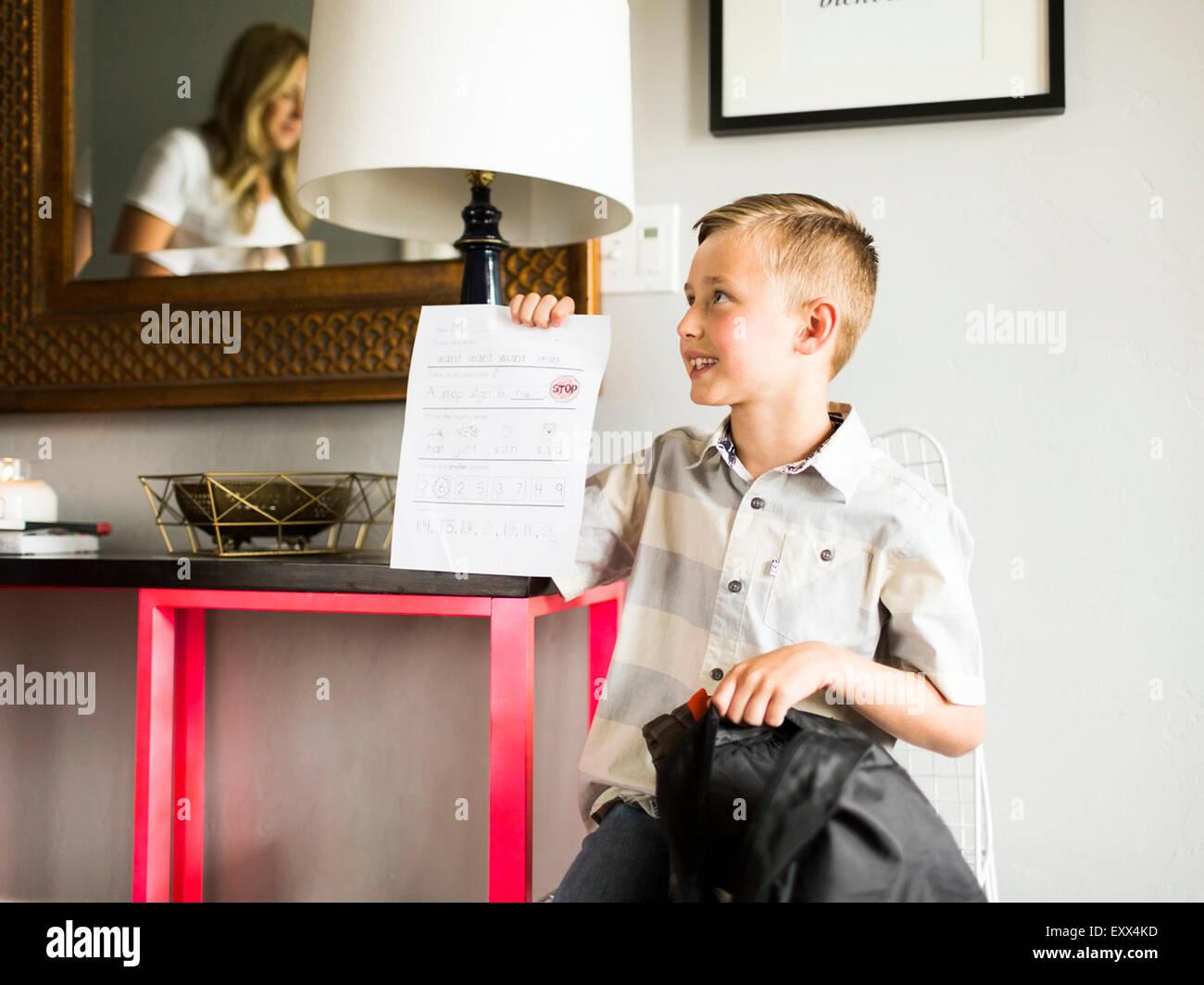 Smiling boy (6-7) showing schoolpaper - Stock Image
