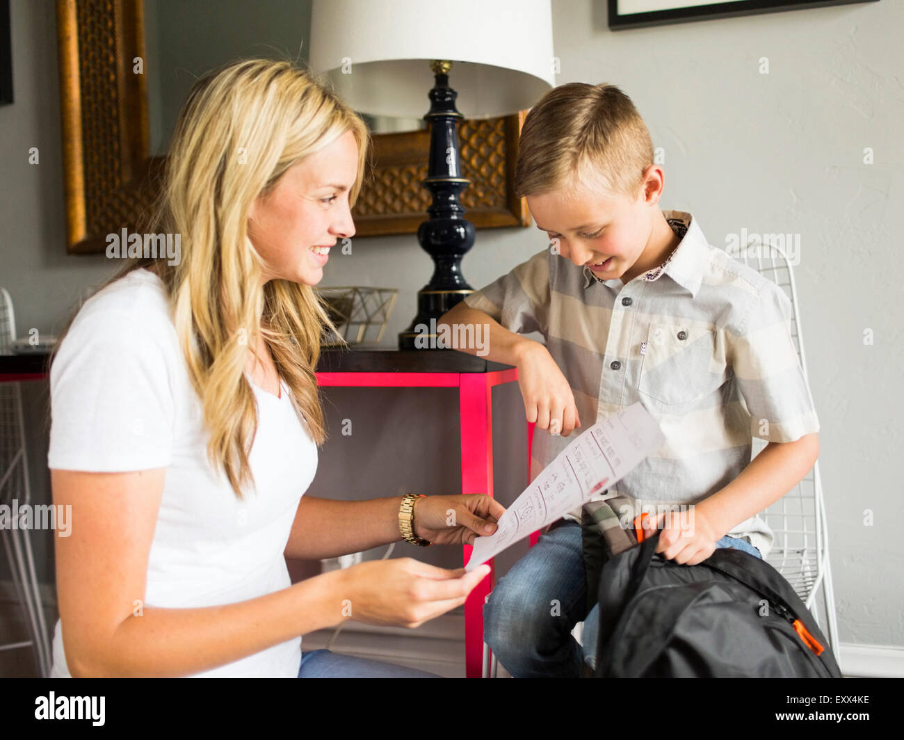 Smiling boy (6-7) showing schoolpaper to mother - Stock Image