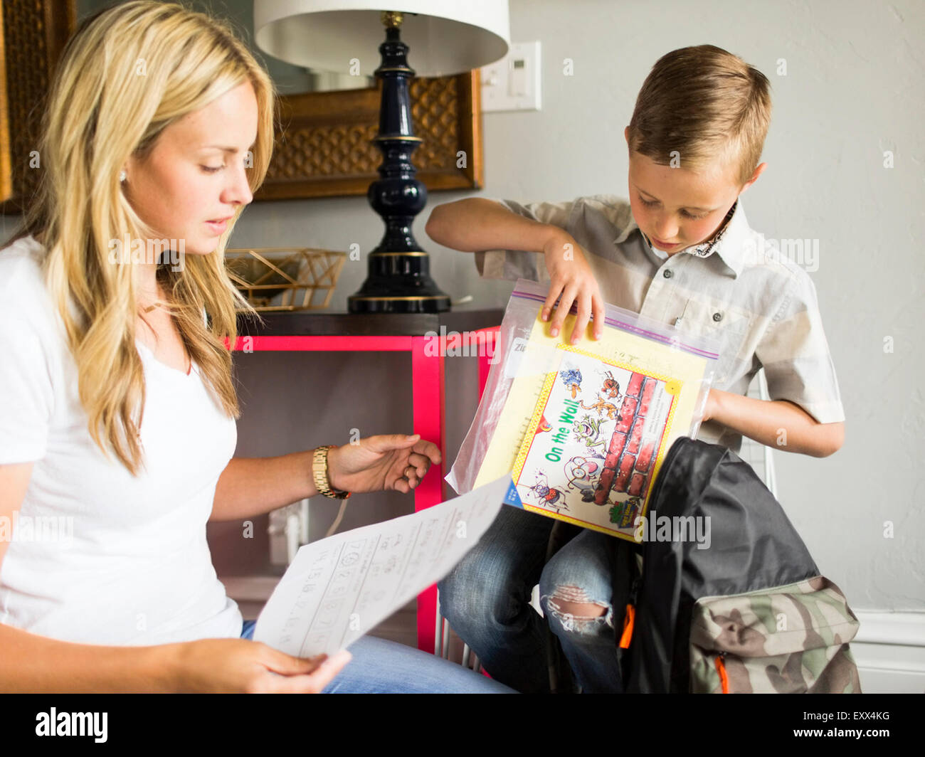 Boy (6-7) showing schoolpaper to mother Stock Photo