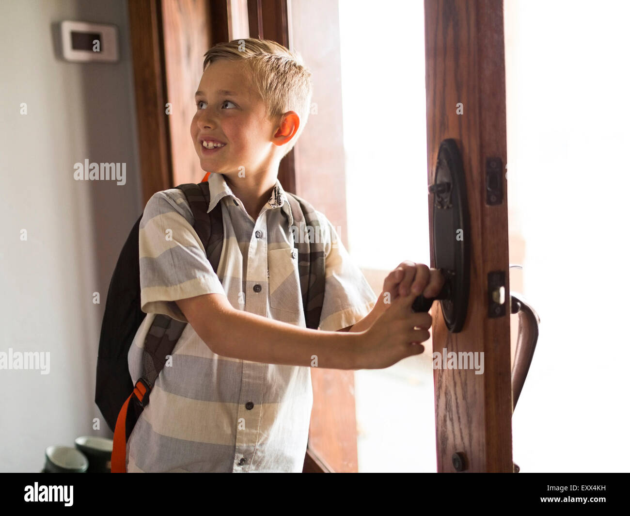 Smiling boy (6-7) leaving for school - Stock Image