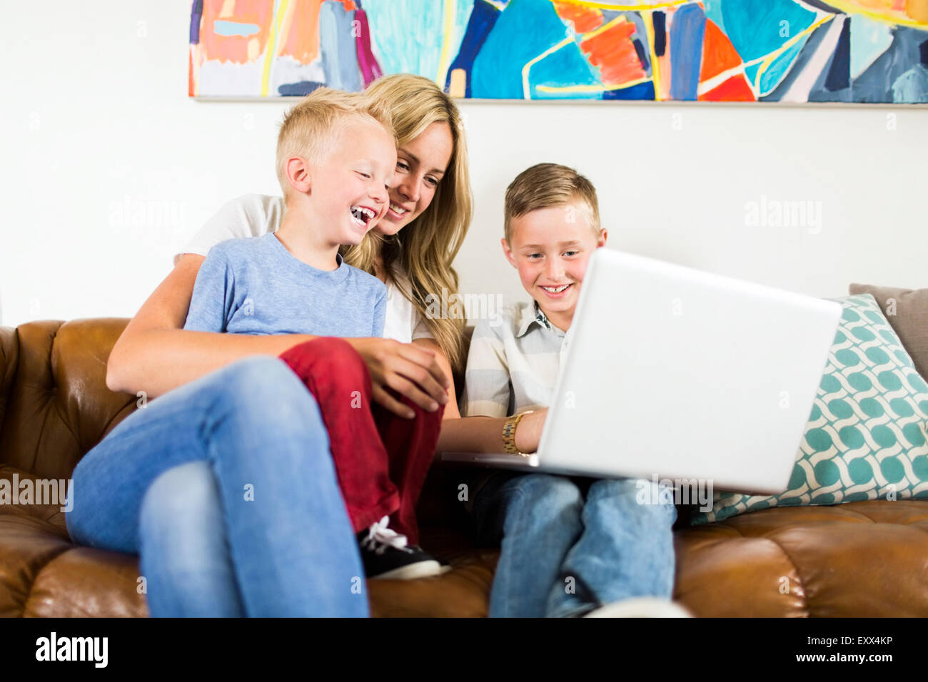 Mother with children (4-5, 6-7) using laptop on sofa Stock Photo