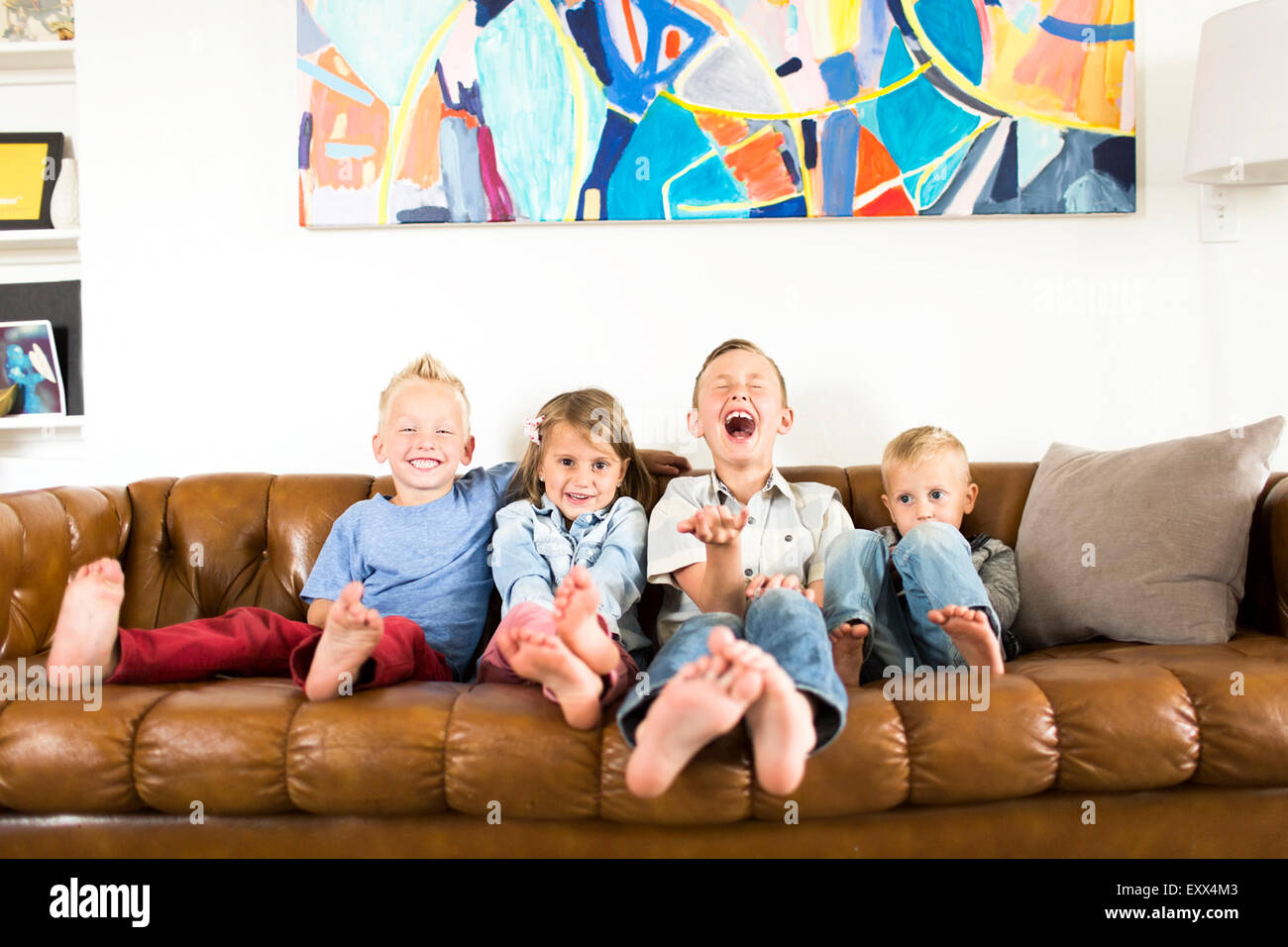 Smiling children (2-3, 4-5, 6-7) sitting on sofa - Stock Image
