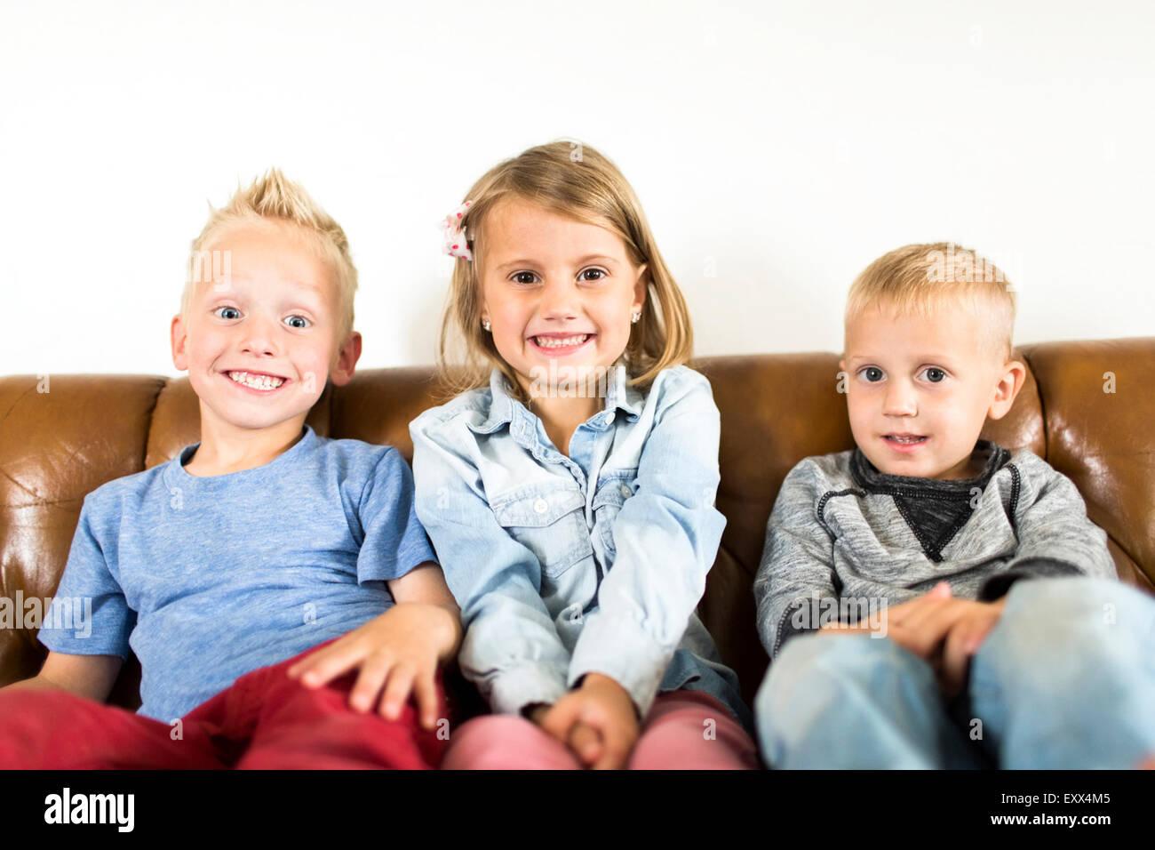 Smiling children (2-3, 4-5) sitting on sofa - Stock Image