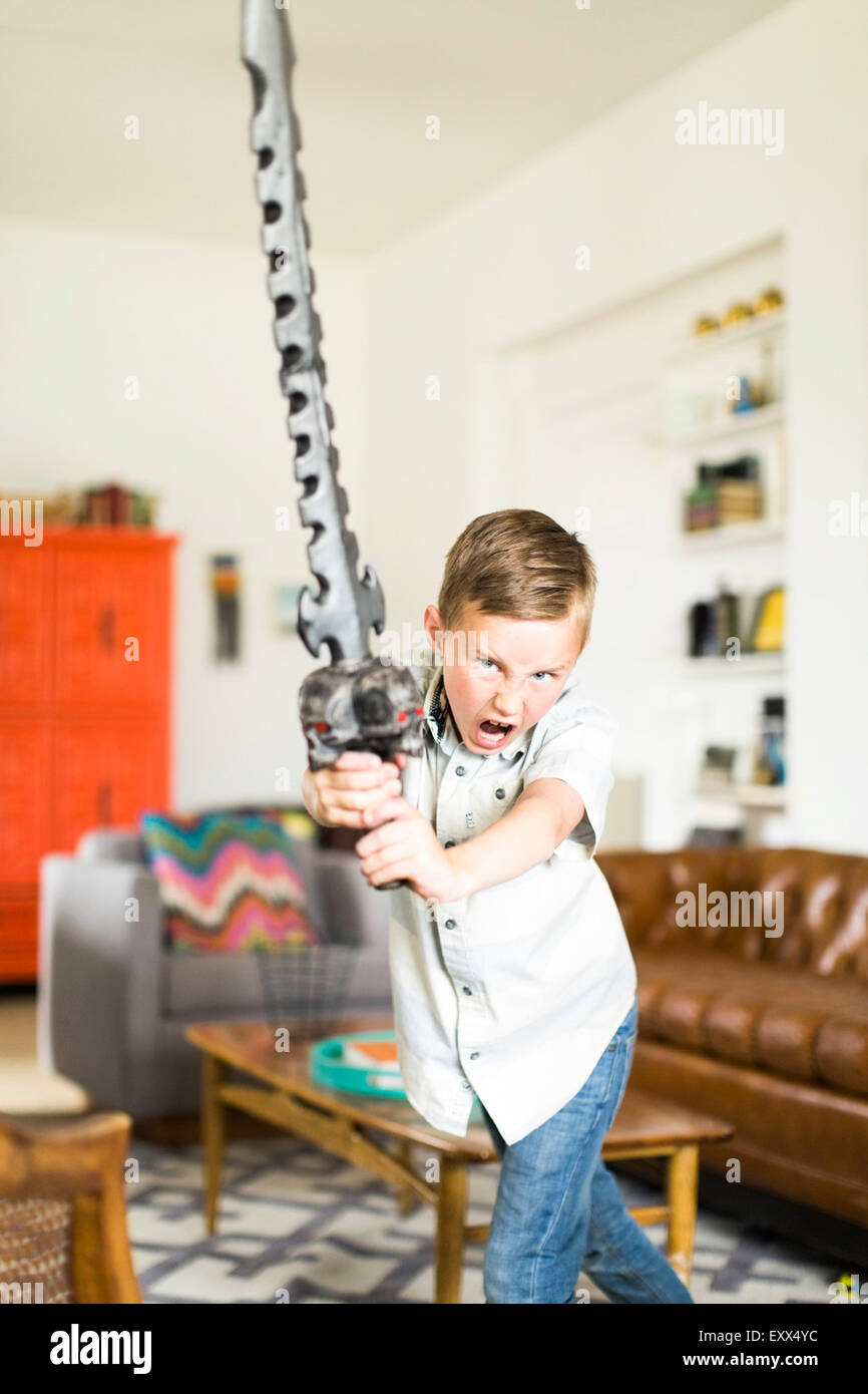 Boy (6-7) playing with sword - Stock Image