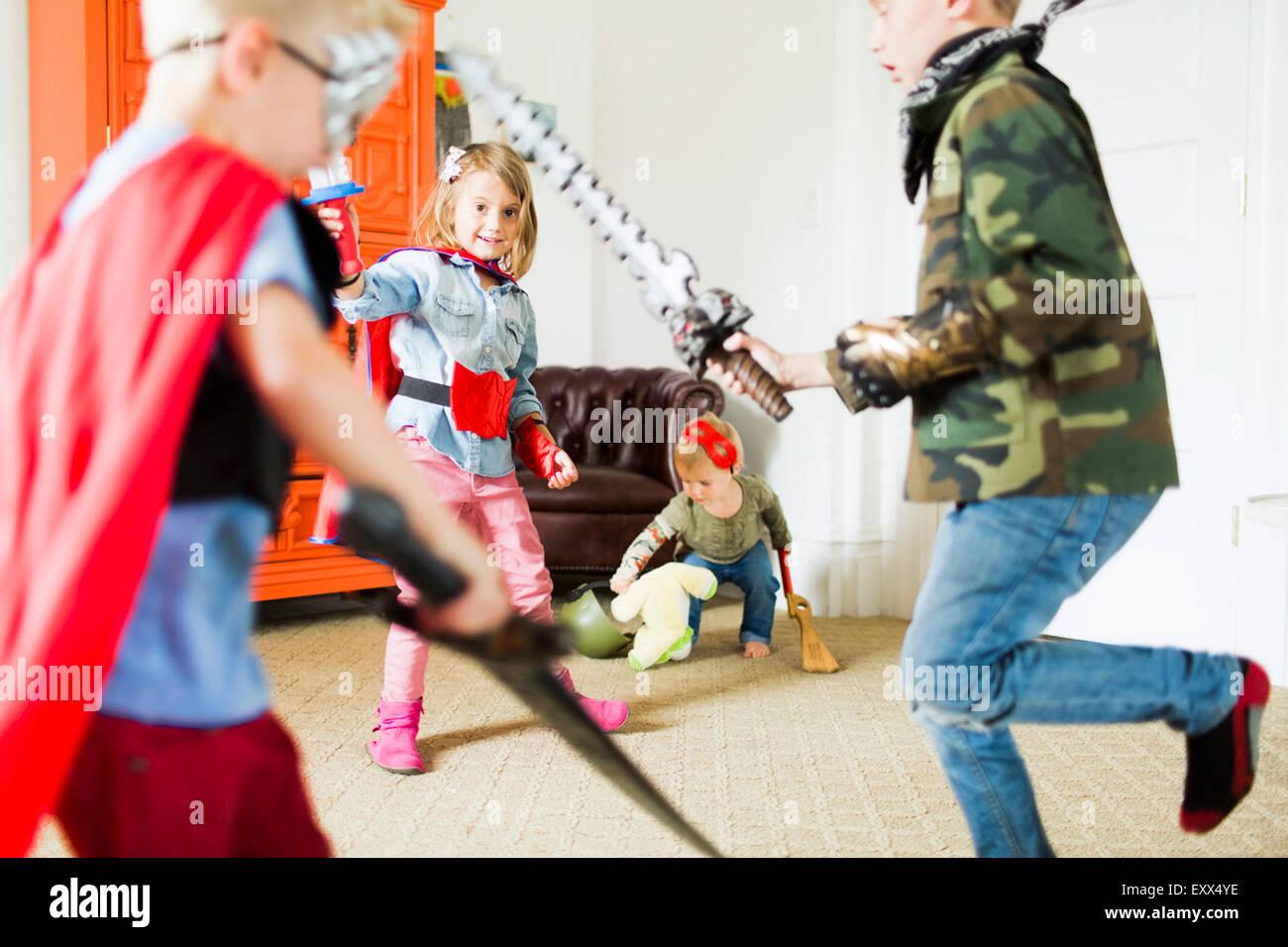 Children (2-3, 4-5, 6-7) wearing superhero costumes playing at home - Stock Image
